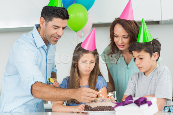 Family of four with cake at a birthday party Stock photo © wavebreak_media