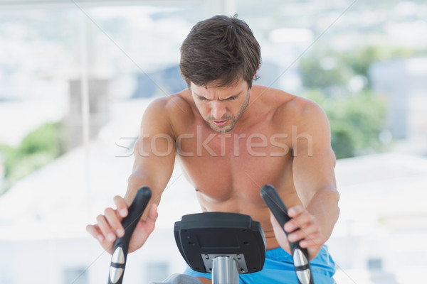 Determined man working out at spinning class in bright gym Stock photo © wavebreak_media