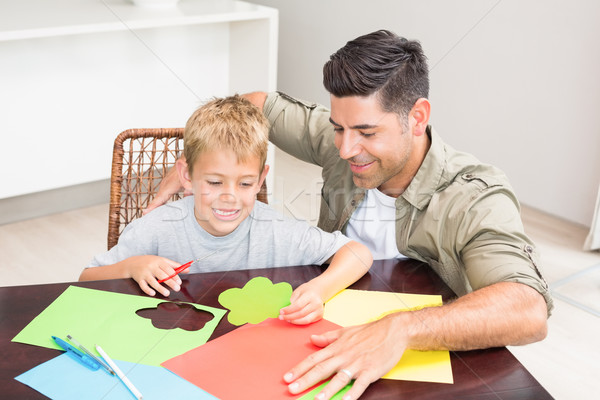 Father and son making paper shapes together at the table Stock photo © wavebreak_media