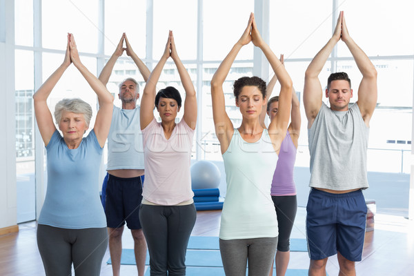 People with eyes closed and joined hands at fitness studio Stock photo © wavebreak_media