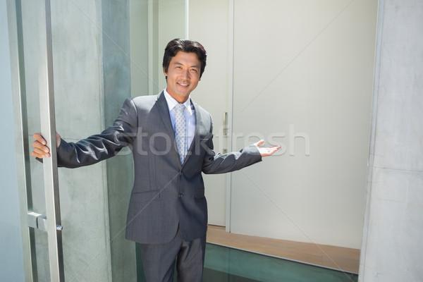 Confident estate agent standing at front door welcoming you in Stock photo © wavebreak_media