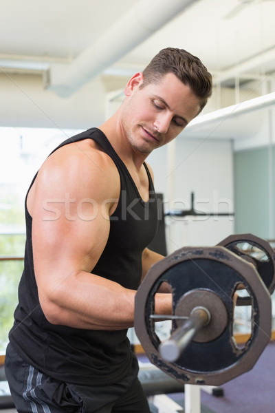 Muscular bodybuilder lifting heavy black barbell weight Stock photo © wavebreak_media