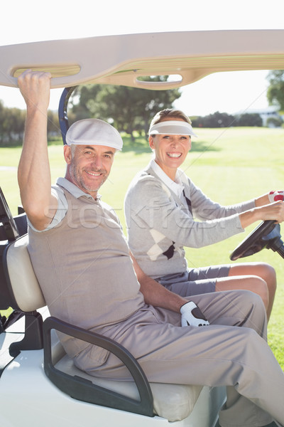 Happy golfing couple smiling at camera in their buggy Stock photo © wavebreak_media