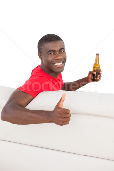 Football fan in red jersey sitting on couch holding beer showing Stock photo © wavebreak_media