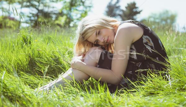 Pretty blonde in sundress sitting on grass Stock photo © wavebreak_media