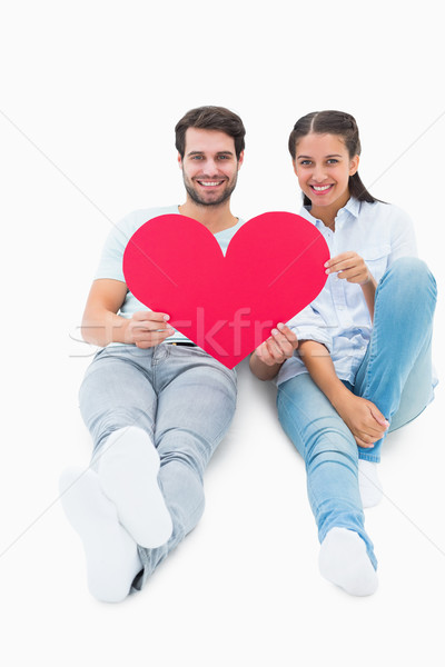 Cute couple sitting holding red heart Stock photo © wavebreak_media