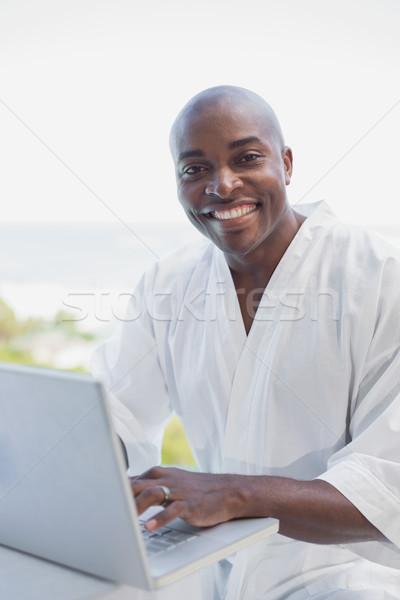 Knappe man badjas met behulp van laptop buiten computer Stockfoto © wavebreak_media