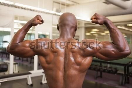 Muscular man measuring waist in gym Stock photo © wavebreak_media