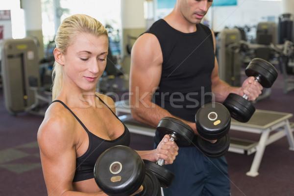 Couple exercising with dumbbells in gym Stock photo © wavebreak_media