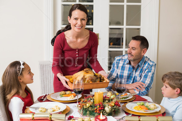 Smiling woman serving roast turkey to her family Stock photo © wavebreak_media