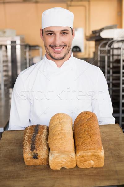 Smiling baker showing loaves of bread Stock photo © wavebreak_media