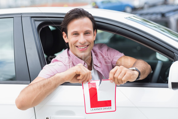 Learner driver smiling and tearing l plate Stock photo © wavebreak_media