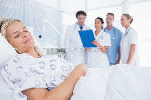 Sleeping patient with doctors behind Stock photo © wavebreak_media