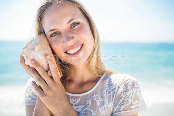 Lovely woman listening to a shell Stock photo © wavebreak_media
