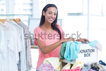 Mosolyog fiatal női önkéntes ruházat portré Stock fotó © wavebreak_media
