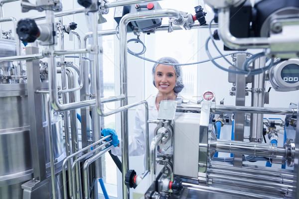 Portrait of a smiling scientist behind metal pipe Stock photo © wavebreak_media