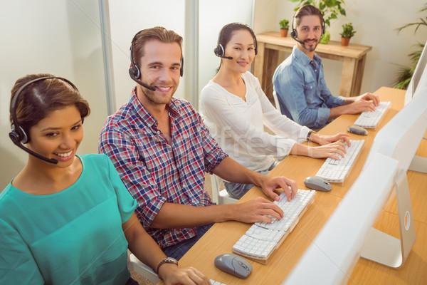 Uśmiechnięty call center zespołu patrząc kamery szczęśliwy Zdjęcia stock © wavebreak_media