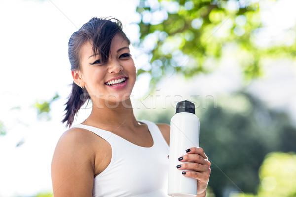 Portret glimlachend atletisch vrouw veldfles Stockfoto © wavebreak_media