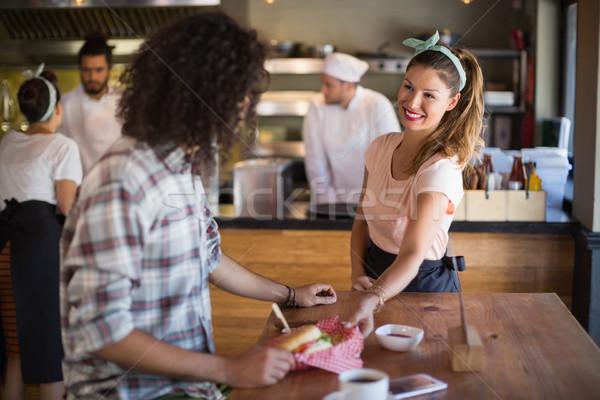 Camarera Burger joven restaurante sonriendo Foto stock © wavebreak_media