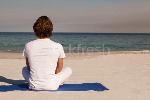 Rear view of man meditating at beach Stock photo © wavebreak_media