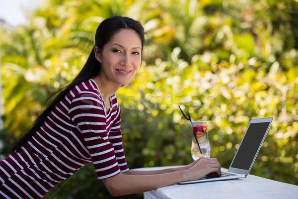 Portrait of young woman using laptop at restaurant Stock photo © wavebreak_media