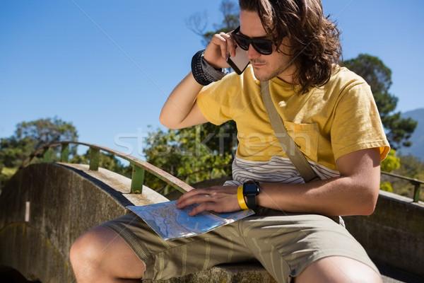 Tourist man with map talking on mobile phone Stock photo © wavebreak_media