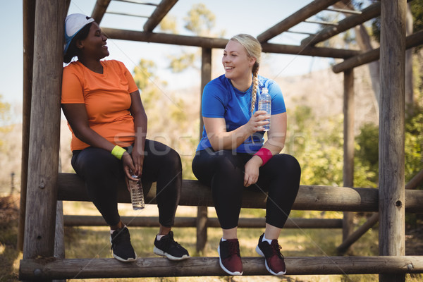 Happy friends holding water bottle while relaxing in boot camp Stock photo © wavebreak_media