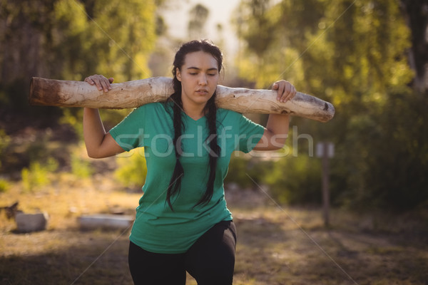 Woman carrying heavy wooden log during obstacle course Stock photo © wavebreak_media