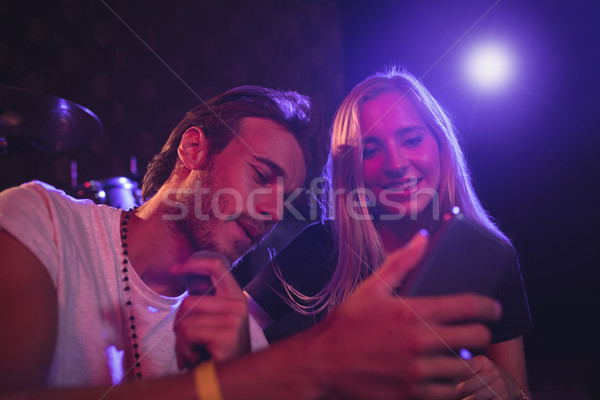 Young male and female musicians using mobile phone in nightclub Stock photo © wavebreak_media
