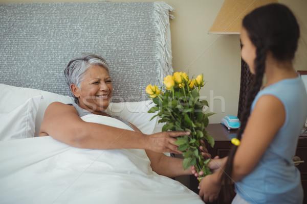 Granddaughter giving flowers to grandmother in bed room Stock photo © wavebreak_media