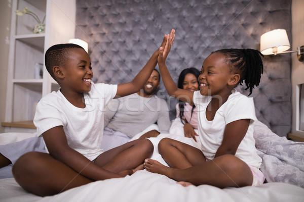 Boldog testvérek pacsi szülők ül ágy Stock fotó © wavebreak_media