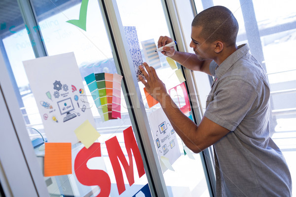 Male executive writing on sticky notes Stock photo © wavebreak_media