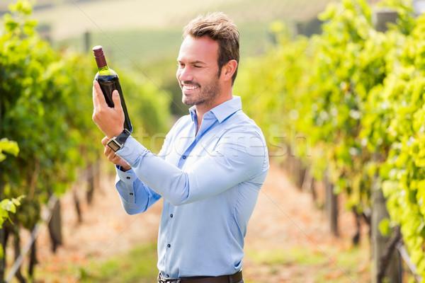 Smiling young man holding wine bottle Stock photo © wavebreak_media