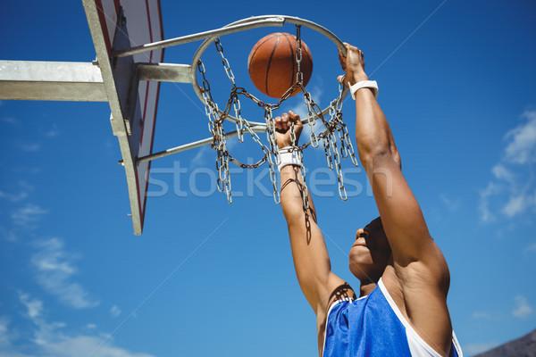 Low angle view of teenager hanging on basketball hoop Stock photo © wavebreak_media