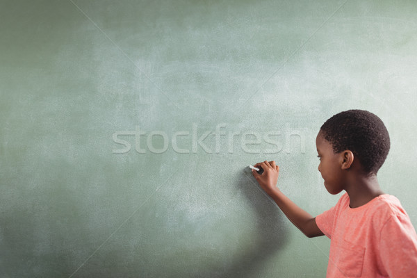 Schoolboy writing on chalkboard Stock photo © wavebreak_media