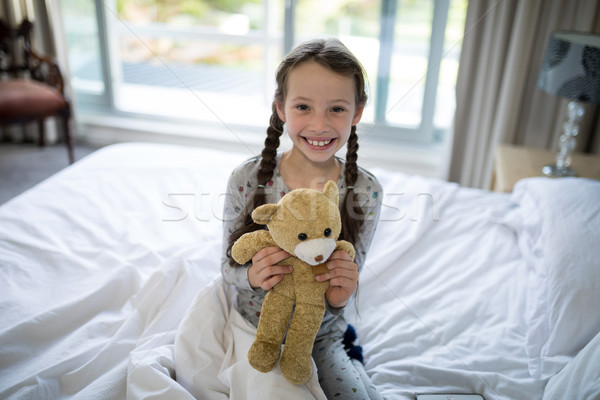 Stock photo: Girl holding teddy bear on bed in bedroom
