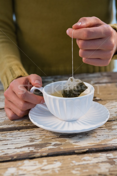 Mid section of woman dipping tea bag in cup at table Stock photo © wavebreak_media