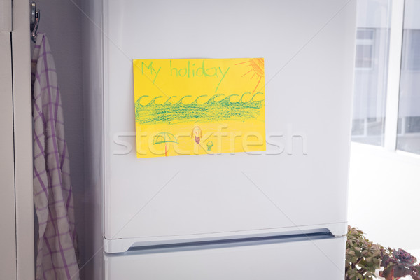 Drawing on yellow paper stuck to refrigerator by window at home Stock photo © wavebreak_media