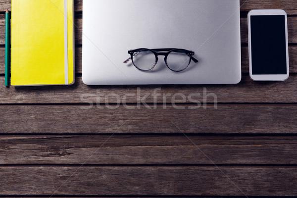 Laptop diário óculos telefone móvel mesa de madeira negócio Foto stock © wavebreak_media