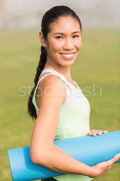 Smiling sporty woman holding exercise mat Stock photo © wavebreak_media