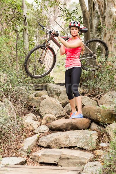 Blonde athlete carrying her mountain bike over rocks Stock photo © wavebreak_media