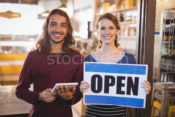 Portrait of smiling waitress holding placard while standing by man with digital tablet Stock photo © wavebreak_media