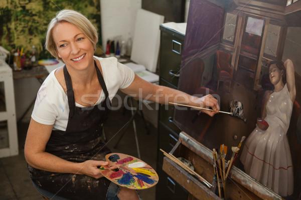 Happy woman painting on canvas Stock photo © wavebreak_media