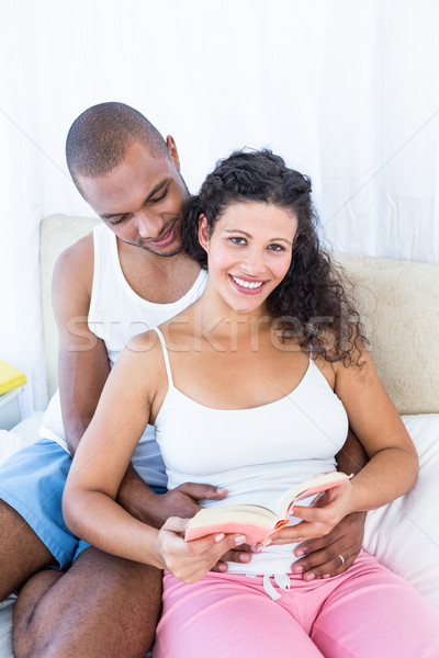 Portrait of pregnant wife holding book with husband on bed Stock photo © wavebreak_media
