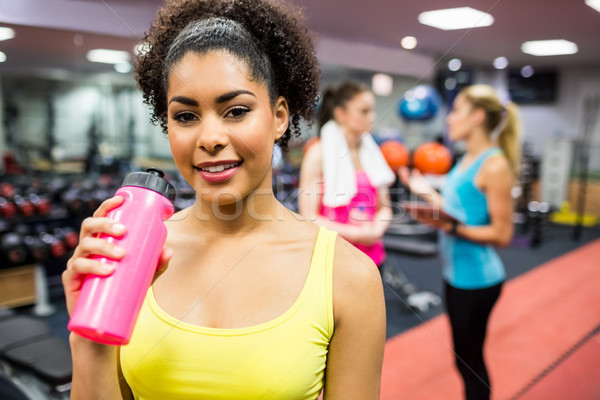 Fit woman smiling at camera in weights room Stock photo © wavebreak_media