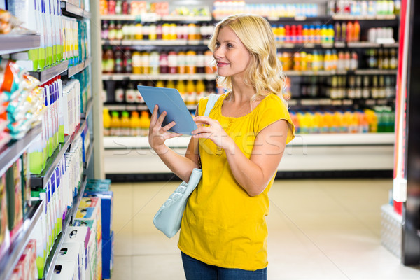 Woman with tablet in aisle  Stock photo © wavebreak_media