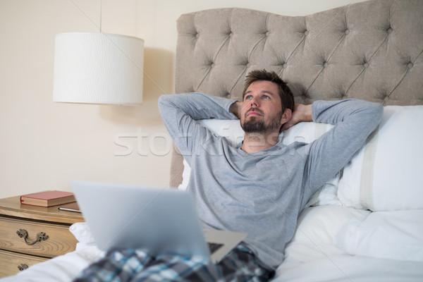 Man using laptop in bed Stock photo © wavebreak_media