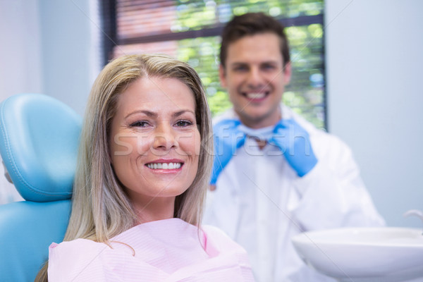 Smiling woman sitting on chair against dentist at medical clinic Stock photo © wavebreak_media