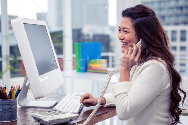 Mosolyog ázsiai nő telefonál hívás számítógéphasználat iroda Stock fotó © wavebreak_media