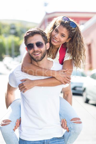 Hip man giving piggy back to his girlfriend Stock photo © wavebreak_media